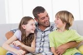 picture of tickle  - Happy father tickling son and daughter while sitting on sofa at home - JPG