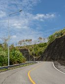 stock photo of light-pole  - Asphalt curve road with lighting pole in sunny day - JPG