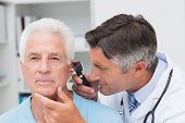image of otoscope  - Male doctor examining senior patients ear with otoscope in clinic - JPG