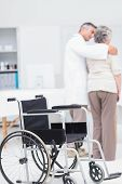 image of wheelchair  - Doctor assisting senior woman to walk with wheelchair in foreground at clinic - JPG