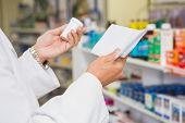image of prescription  - Pharmacist reading prescription and holding medicine in the pharmacy - JPG