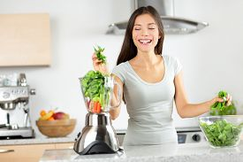 stock photo of blender  - Green smoothie woman making vegetable smoothies with blender home in kitchen - JPG