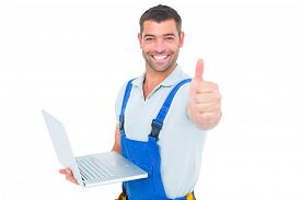 stock photo of handyman  - Portrait of handyman with laptop gesturing thumbs up on white background - JPG