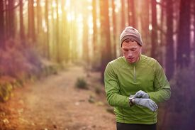 picture of cardio exercise  - Trail running runner looking at heart rate monitor watch running in forest wearing warm jacket sportswear - JPG