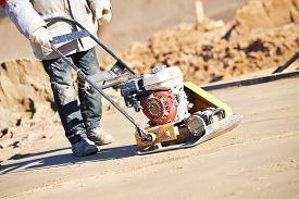 picture of vibration plate  - builder worker at sand ground compaction with vibration plate compactor machine before pavement roadwork - JPG