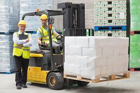 foto of forklift  - Driver operating forklift machine next to his manager in warehouse - JPG