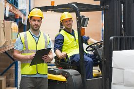 foto of forklift  - Smiling warehouse worker and forklift driver in warehouse - JPG