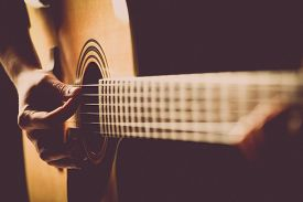 picture of classic art  - Color detail of hands playing of an old acoustic guitar.