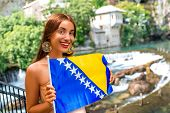 stock photo of cave woman  - Woman with Bosnian flag in Blagaj village - JPG
