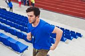 stock photo of upstairs  - Sporty young man runner on stadium running upstairs with blue seats on stadium and people on background - JPG