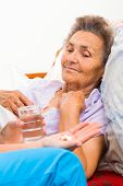 stock photo of nurse  - Nurse giving medication to elderly patient in nursing home - JPG