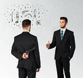 stock photo of backstabbers  - Ruthless businessman handshake with hiding a weapon and weapon symbols around his head - JPG