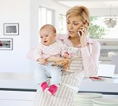 picture of people talking phone  - Casual caucasian housewife in kitchen with baby - JPG
