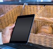 stock photo of tong  - Man using tablet pc against baskets with breads freshly baked and tongs - JPG