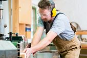stock photo of carpenter  - Carpenter working on an electric buzz saw cutting some boards - JPG