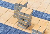 picture of pedestrians  - Pile of yellow bricks and paved pedestrian path - JPG