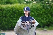 foto of girth  - Horserider with harness before training at summer time - JPG