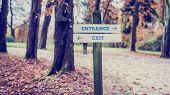 Постер, плакат: Signpost With Arrows Pointing Two Opposite Directions Towards Entrance And Exit