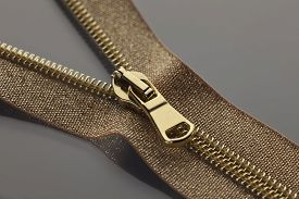 picture of zipper  - studio photography of golden brown zipper opened on a half to a gray surface - JPG