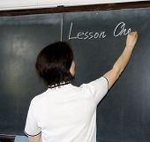 Female Teacher Writing On A Blackboard