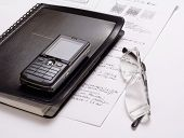 Various office supplies - Documents and mobile phone on desk - office equipment