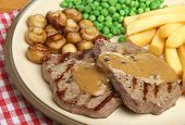 Chargrilled rump steak with pepper sauce, chips, peas and mushrooms.