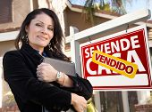 Proud, Attractive Hispanic Female Agent In Front of Spanish Vendido Se Vende Casa Real Estate Sign and House.
