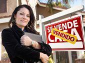 Orgulhoso, atraente agente feminino latino-americano na frente do sinal de imobiliário espanhol Vendido Se Vende Casa um