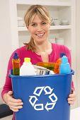 Mulher segurando Bin de reciclagem de lixo em casa