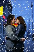 Young loving couple kissing in a winter city.