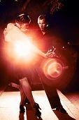 Beautiful couple dancing tango on night street, dramatic light.