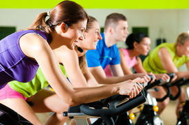 foto of exercise bike  - Group of five people in gym or fitness club exercising their legs doing cardio training - JPG