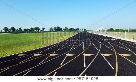 poster of Eight Lane Black Asphalt Running Track In Stadium Black And White. Running Track On Blue Sky. Runnin