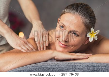 poster of Senior woman in spa salon getting massage. Closeup of a beautiful woman during spa treatment. Beauti