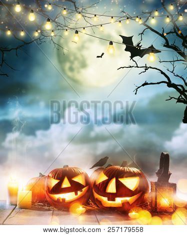 poster of Spooky halloween pumpkins on wooden planks with dark horror background. Celebration theme, copyspace