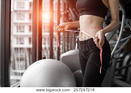 poster of Sporty Woman Using Waist Tape Line In Fitness Gym Sport Club Training Center Near Window With Condom
