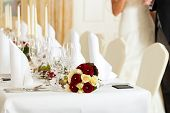 stock photo of wedding feast  - Wedding table at a wedding feast decorated with bridal bouquet - JPG