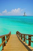 Dock Leading to Beautiful ocean Water with Sailboat on Horizon