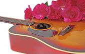 Acoustic guitar with bouquet of red flowers