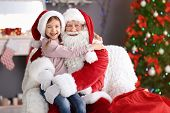 Little Girl Sitting On Authentic Santa Claus Lap Indoors poster