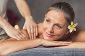 Senior woman in spa salon getting massage. Closeup of a beautiful woman during spa treatment. Beauti poster