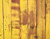 Old wooden fence painted yellow with paint chipping and wear