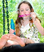 stock photo of swingset  - Young girl outside blowing bubbles while sitting on tire swing - JPG