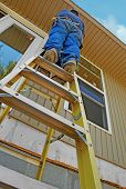 picture of home addition  - Construction worker high up on ladder - JPG