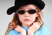 Young girl looking serious in sunglasses and black cap