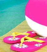 Beachball rosa e branco com muito chinelos na doca