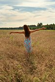Young Woman Girl Standing With Her Back With Open Arms To The Sunset On A Wheat Field In The Country poster