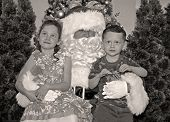 Young boy and girl sitting on Santa Claus' lap