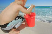 Young toddler boy playing with sand bucket at seashore