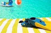 Aletas da natação e brinquedos, toalha de praia e piscina